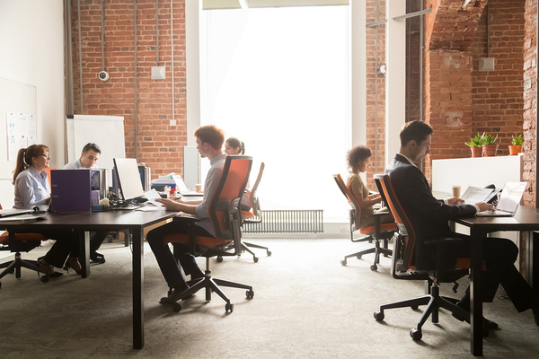 Group of people working in an open office space.